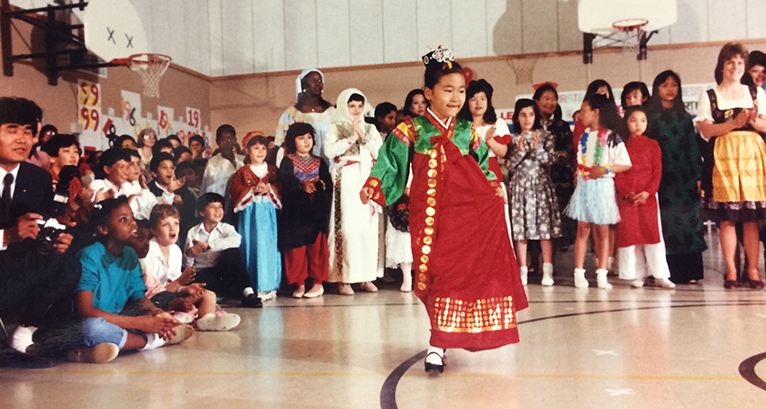 Color photograph from Parklawn Elementary School's 30th anniversary celebration. Similar to a modern International Festival at Parklawn, the children are dressed in traditional clothing from the country of their native heritage. A girl in a red and green dress parades before a diverse crowd of students and parents gathered in the school's gymnasium.