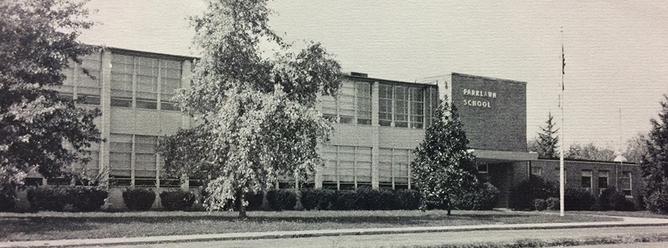 Black and white photograph of the main entrance and front of Parklawn Elementary School from our 1975 – 1976 yearbook. Unlike the image at the top of this page, the trees and shrubs appear full grown.